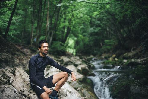 Caucasian man sitting on rocks near forest stream - BLEF03135