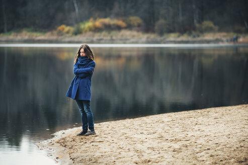 Caucasian woman wearing blue coat and scarf near lake - BLEF03147
