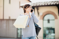 Female shopper using smartphone in piazza, Arezzo, Toscana, Italy - CUF51116