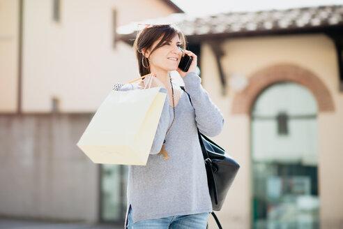 Female shopper using smartphone in piazza, Arezzo, Toscana, Italy - CUF51116