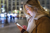 Young woman using smartphone touchscreen on city street at night, Madrid, Spain - CUF51146