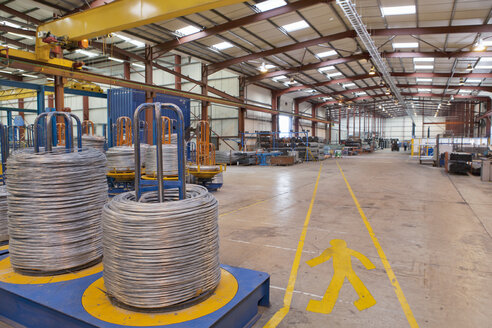 Coiled cable next to pedestrian walkway in warehouse - JUIF00912