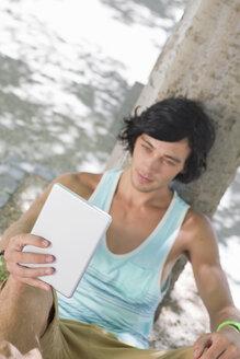 Young man using digital tablet against tree in park - JUIF00918