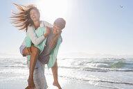 Man piggybacking enthusiastic woman on sunny beach - JUIF00930