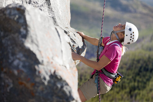 Female rock climber scaling rock face and looking up - JUIF00933