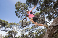 Woman jumping with mountain bike over log in woods - JUIF00957