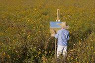 Senior woman painting in sunny wildflower meadow - JUIF00981