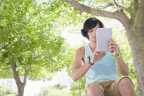 Young man using digital tablet below tree in park - JUIF00993