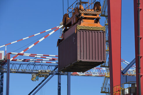 Crane lifting cargo container at commercial dock - JUIF00999