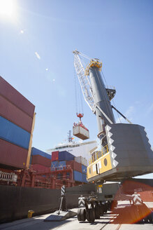 Crane unloading container ship at commercial dock - JUIF01005