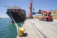 Crane unloading container ship at commercial dock - JUIF01008