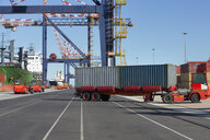 Truck moving cargo containers at commercial dock - JUIF01020