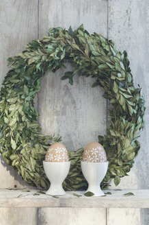 Two painted Easter eggs in egg cups and box tree wreath on shelf in front of wooden wall - ASF06398