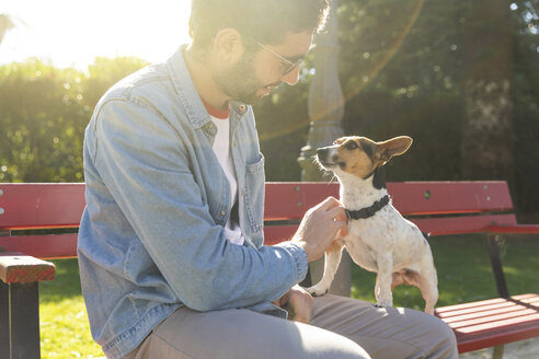Young man sitting on park bench tickling his dog - WPEF01502