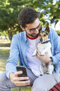 Young man sitting on park bench with his dog taking selfie with smartphone - WPEF01505