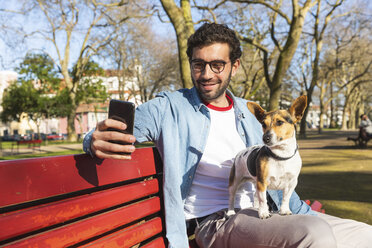 Portrait of young man sitting with his dog on park bench taking selfie with smartphone - WPEF01514