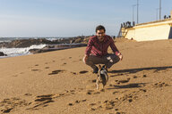 Portugal, Porto, young man playing on the beach with his dog - WPEF01520