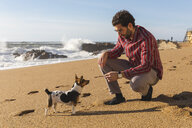 Portugal, Porto, young man playing with his dog on the beach - WPEF01523