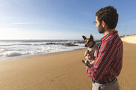 Portugal, Porto, content young man on the beach with his dog - WPEF01526
