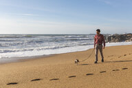 Portugal, Porto, young man strolling on the beach with his dog - WPEF01529