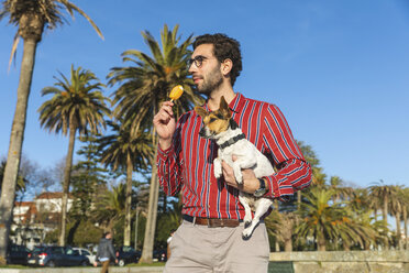 Young man with dog on his arm eating ice lolly - WPEF01535