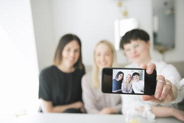 Happy friends taking selfie in a restaurant - AHSF00375