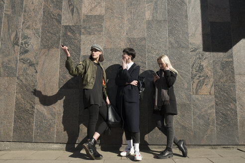 Three young women standing at a wall in the city talking - AHSF00393
