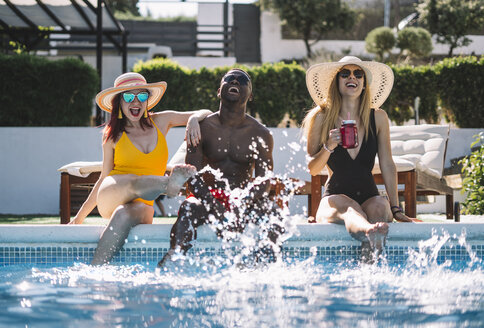 Two beautiful women and african man sitting on the edge of the pool. - OCMF00449