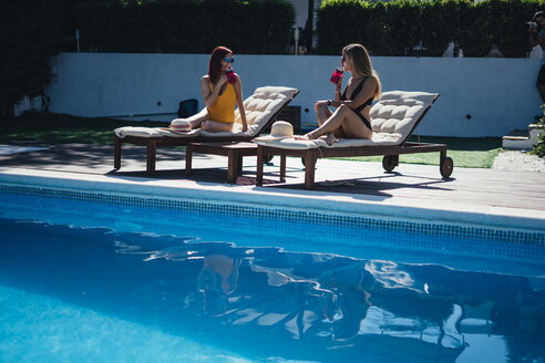 Two beautiful women relaxing on a terrace next to the pool - OCMF00452