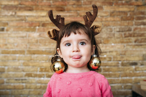 Portrait of toddler girl sticking out tongue wearing reindeer antlers headband and Christmas baubles - GEMF02943