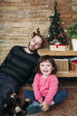 Exhausted father wearing reindeer antlers sleeping next to Christmas tree and laughing toddler girl - GEMF02946