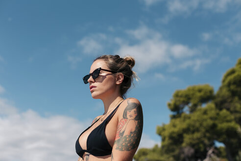 Attractive woman with tattoos wearing a black bikini and sunglasses, sunbathing outdoors. Mallorca, Balearic Islands, Spain. - LOTF00071