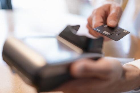 Man using credit card reader, close-up - DIGF07028