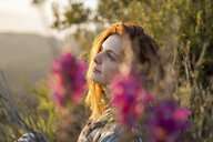 Dreaming redheaded woman in nature at sunset - AFVF02939