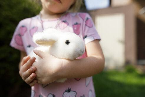 Close-up of girl holding toy bunny outdoors - KMKF00949