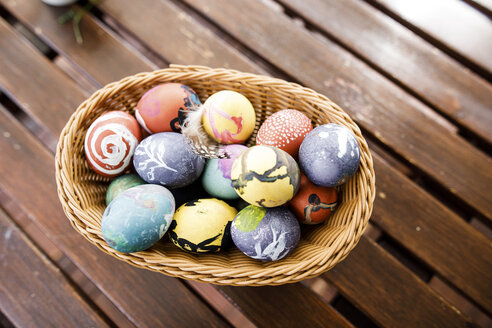 Easter eggs in basket on wooden table - KMKF00952