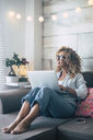 Woman using laptop on couch at home - SIPF01959