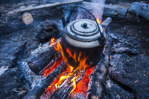 Boiling water pot over an open fire on a campsite on Tolbachik volcano, Kamchatka, Russia - RUNF02029