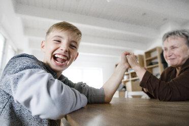Happy grandson and grandmother arm wrestling - KMKF00960