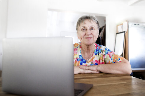 Portrait of smiling senior woman sitting at table at home using laptop - KMKF00963