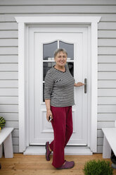 Smiling senior woman standing on porch of her house - KMKF00966