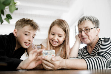 Happy grandmother and grandchildren using  cell phone at home - KMKF00972