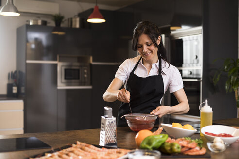 Woman straining a sauce while cooking in a kitchen in Madrid - ABZF02351