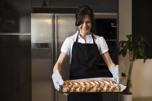 Smiling woman holding a baking tray with shrimps in kitchen - ABZF02360