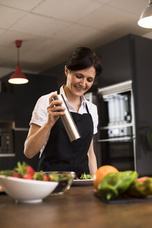 Woman pouring pepper on a dish in a kitchen in Madrid, Spain - ABZF02366