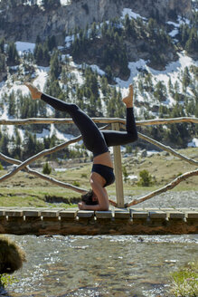 Young woman doing yoga in nature, headstand - JPF00386