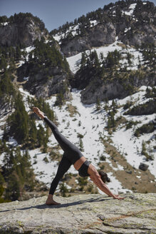 Young woman doing yoga in nature, downward facing dog pose - JPF00395