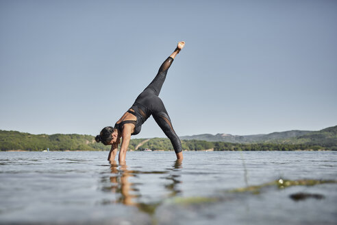 Young woman doing yoga in nature, downward facing dog pose - JPF00401