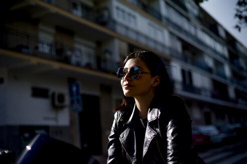 Portrait of young motorcyclist wearing sunglasses at evening twilight - OCMF00455