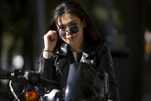 Portrait of young woman motorcyclist wearing sunglasses and black leather jacket - OCMF00458